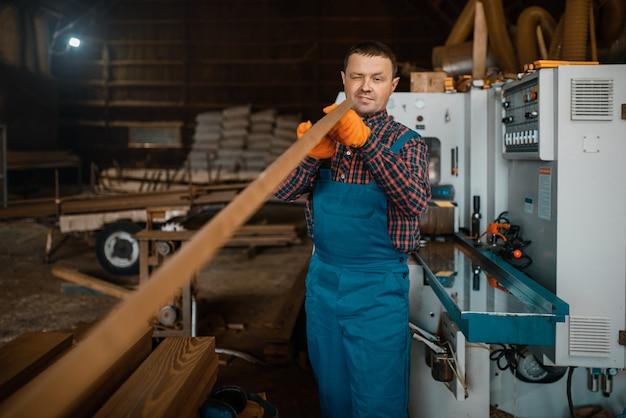 Zimmermann in uniform arbeitet an holzbearbeitungsmaschine, holzindustrie, zimmerei. holzverarbeitung in der fabrik