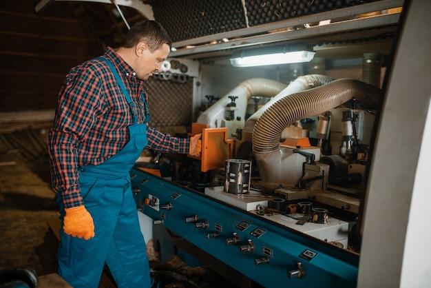 Zimmermann in uniform in der nähe von holzbearbeitungsmaschine, holzindustrie, zimmerei. holzverarbeitung auf fabrik, waldsägen im holzplatz