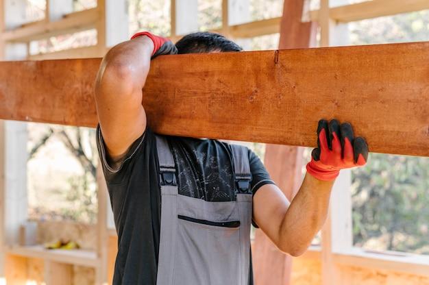 Zimmermann mann, der eine große planke hält