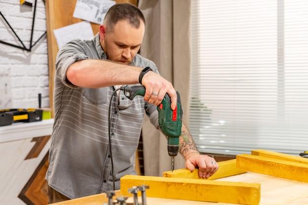 Zimmermann mit bohrmaschine beim bohren von holzbrettern in der werkstatt