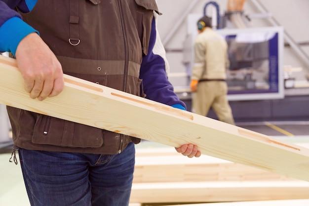 Zimmermann mit einem gehobelten brett in den händen