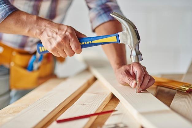 Zimmermann mit hammer auf nägel schlagen