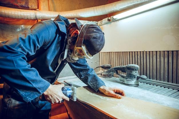 Zimmermann mit kreissäge zum schneiden von holzbrettern