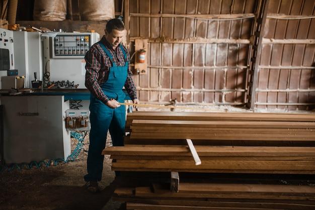 Zimmermann mit maßband bretter, holzbearbeitungsmaschine, holzindustrie, zimmerei. holzverarbeitung auf fabrik, waldsägen im holzplatz