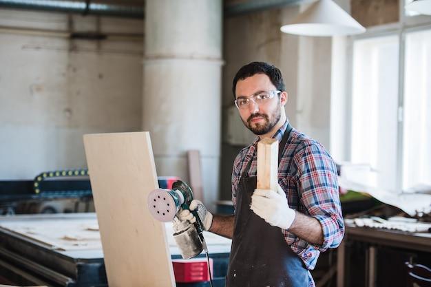 Zimmermann mit schleifmaschine in seiner werkstatt
