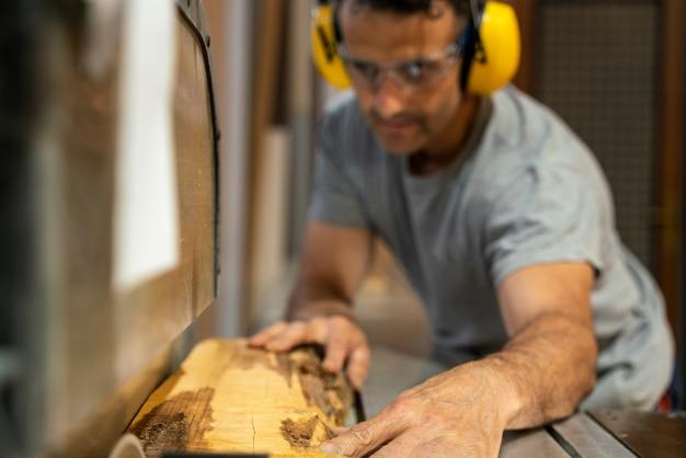 Zimmermann schneidet holz mit einer maschine, die ohrstöpsel trägt.