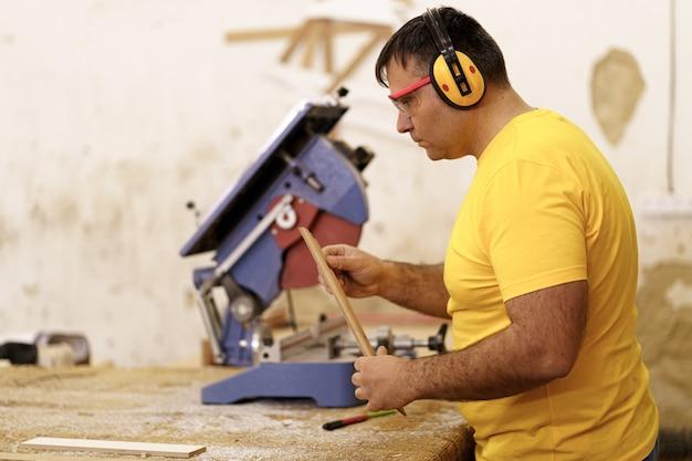 Zimmermann schneidet in seiner holzwerkstatt ein stück holz für möbel, verwendet eine kreissäge und trägt eine schutzbrille und ohrenschützer.