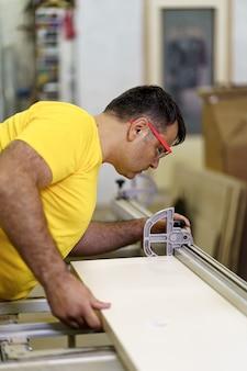 Zimmermann schneidet in seiner holzwerkstatt ein stück holz für möbel, verwendet eine kreissäge und trägt eine schutzbrille.