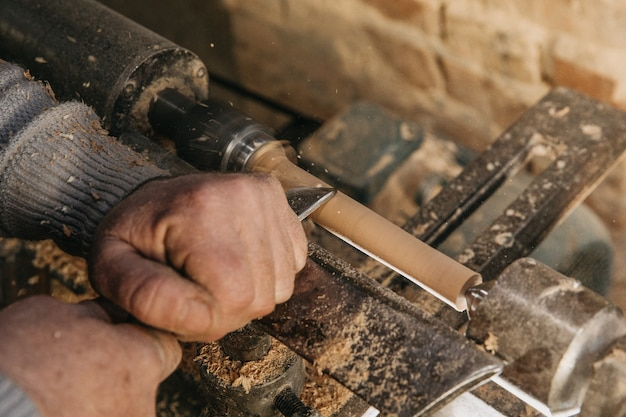 Zimmermann verwendet holz, um skulpturen im atelier zu machen