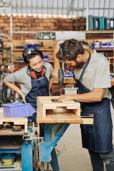 Zimmermann zeigt weiblichen lehrling, wie man holzschublade zusammenbaut