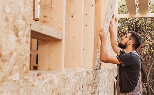 Zimmermannmann, der an einer wand arbeitet