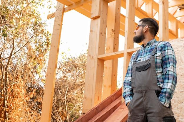 Zimmermannmann, der die hölzerne konstruktion betrachtet