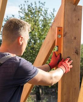 Zimmermannmann, der maßnahmen auf einem holzbrett nimmt
