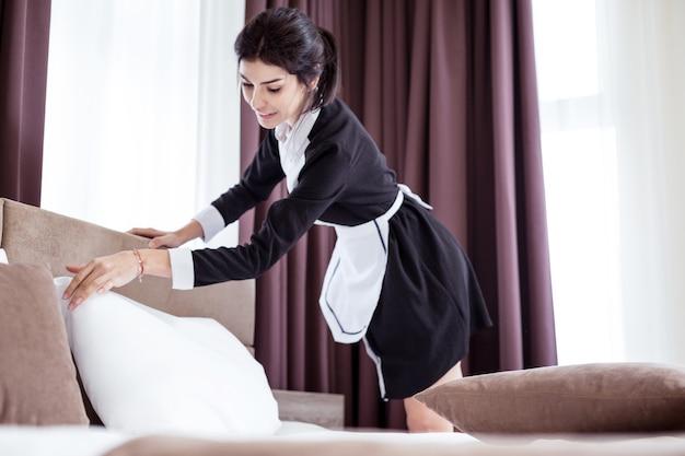 Zimmerreinigung. nette junge frau, die ein kissen auf dem bett berührt, während hotelzimmer säubert