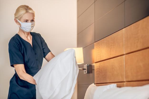 Zimmerservice. blonde frau in einer schutzmaske, die in einem hotelzimmer bett macht