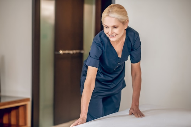 Zimmerservice. blonde hübsche frau in uniform, die in einem hotelzimmer bett macht