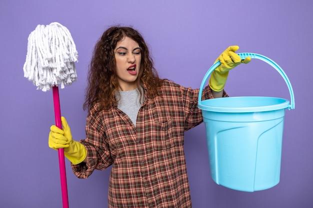 Zimperliche junge putzfrau mit handschuhen, die einen mopp hält und den eimer in der hand isoliert auf lila wand betrachtet