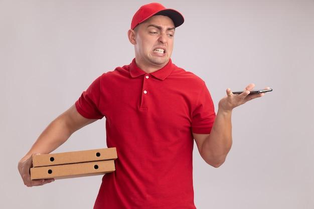 Zimperlicher junger lieferbote, der uniform mit kappe hält, die pizzaschachteln hält und telefon in seiner hand lokalisiert auf weißer wand betrachtet