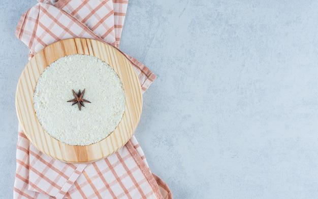 Zimt auf haferbrei in holzteller auf handtuch auf marmor.