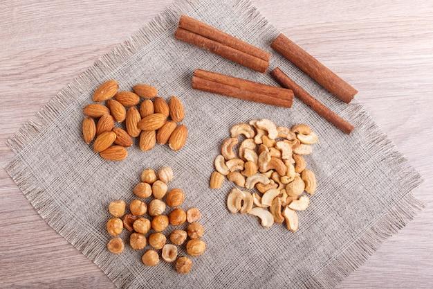 Zimt, mandeln, haselnüsse, cashewnüsse auf einer leinenserviette.