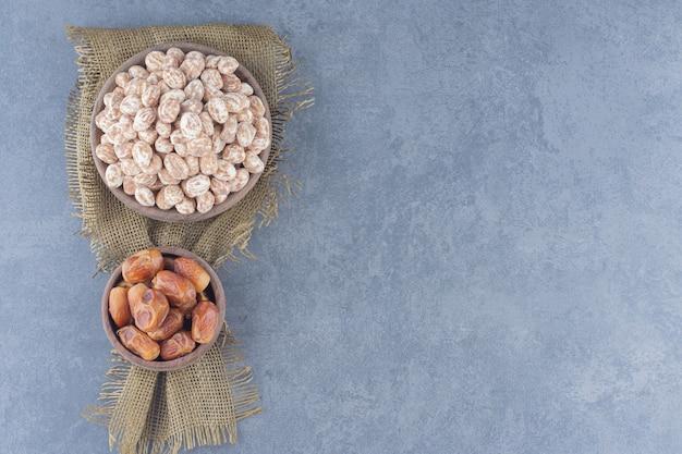 Zimtbonbons und dattelfrüchte auf dem marmorhintergrund.