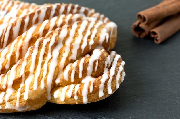Zimtbrötchen oder zimtbrötchen dessert auf schwarzem schieferbrett klassische amerikanische oder französische bäckereien bokeh