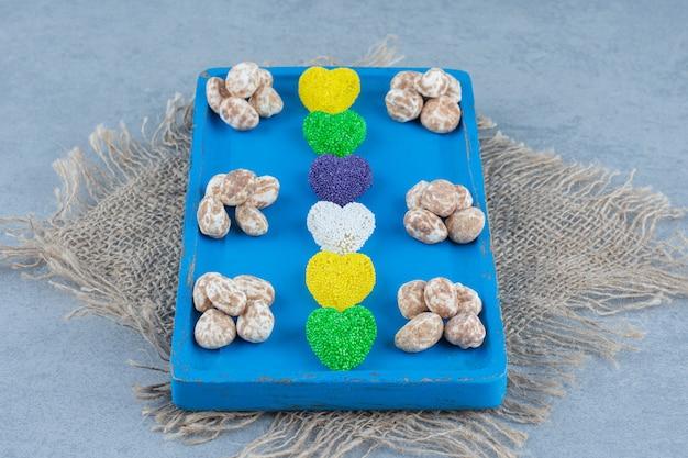 Zimtkonfekt mit keks auf dem brett, auf dem untersetzer, auf dem marmortisch.