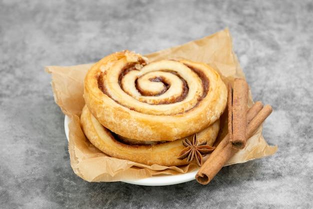 Zimtschnecke mit zimtstangen auf holztisch, dänischem gebäck, süßem gebäck zum frühstück oder snack.