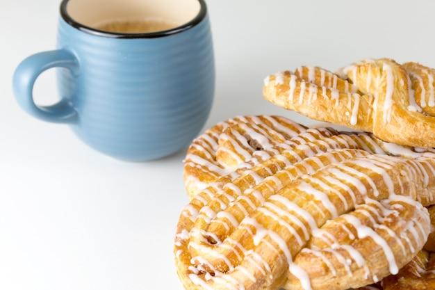 Zimtschnecke oder zimtbrötchen auf teller mit blauer tasse kaffee klassische amerikanische oder französische bäckereien