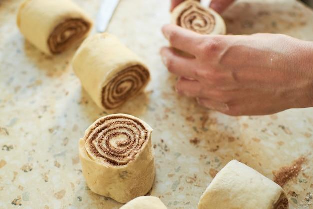 Zimtschnecken - cinnabon kochprozess roher teig. lebensmittelhintergrund