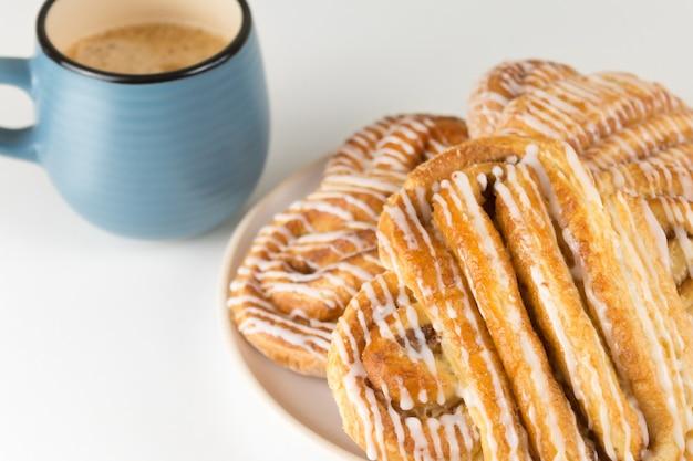Zimtschnecken oder brötchen auf teller mit blauer tasse kaffee klassische amerikanische oder französische bäckereien