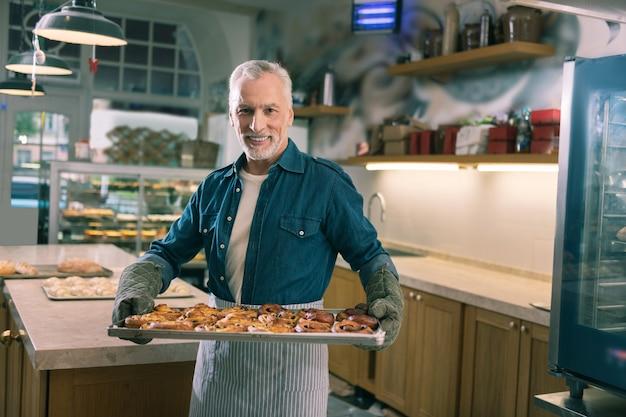Zimtschnecken. strahlender grauhaariger bäcker, der sich zufrieden fühlt, während er das ganze tablett mit schönen zimtschnecken hält
