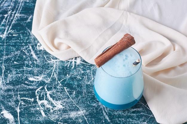 Zimtstange mit einer tasse getränk auf blau.