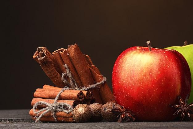 Zimtstangen, äpfel muskatnuss und anis auf holztisch auf brauner oberfläche