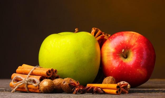 Zimtstangen, äpfel muskatnuss und anis auf holztisch