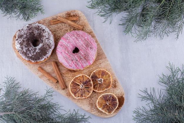Zimtstangen, donuts und getrocknete orangenscheiben auf einem brett auf weißem hintergrund.