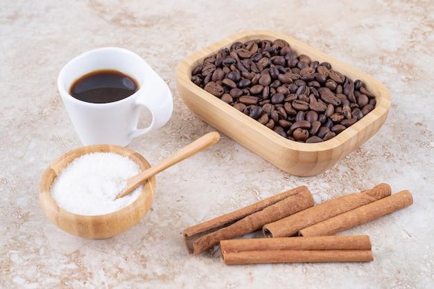 Zimtstangen, kaffeebohnen, zucker und eine tasse kaffee