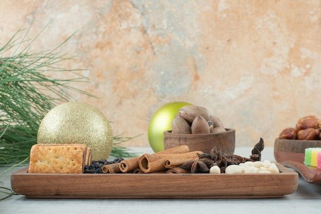 Zimtstangen mit crackern und weihnachtskugeln auf marmorhintergrund. hochwertiges foto