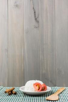 Zimtstangen; spachtel und platte des weißen reises mit tomate schneiden auf tischset gegen hölzernen hintergrund