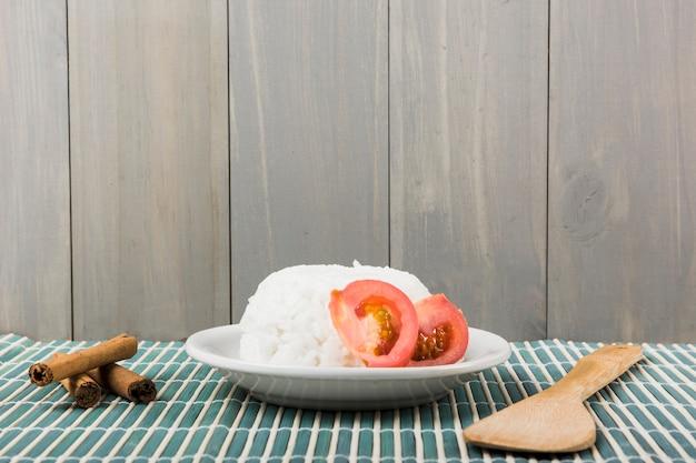 Zimtstangen; spachtel und teller mit weißem reis mit tomatenscheibe auf tischset