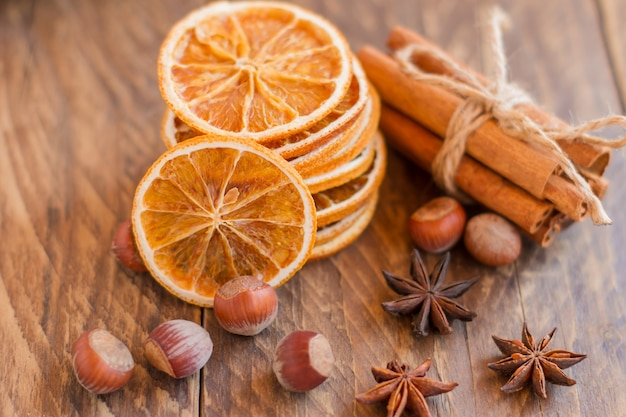 Zimtstangen, trockene orangen und anis auf holztisch, zutaten für glühwein oder backen.