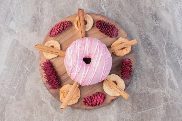 Zimtstangen und getrocknete apfelscheiben um einen donut auf einem mit tannenzapfen geschmückten brett auf marmor.