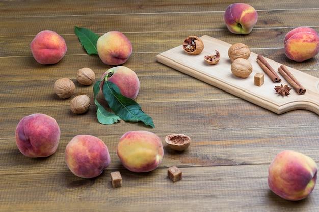 Zimtstangen walnüsse und sternanis auf holzbrett. pfirsiche auf dem tisch. hölzerner hintergrund. ansicht von oben