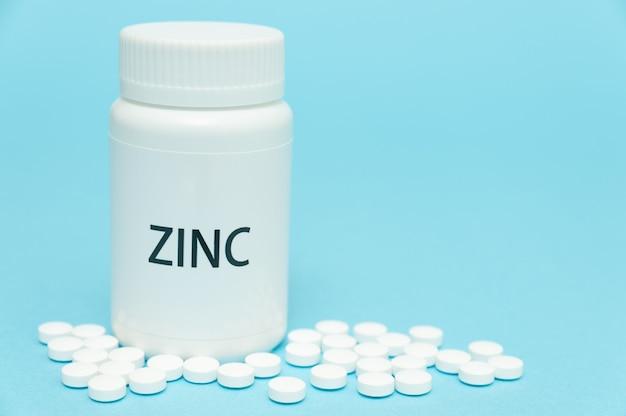 Zink nahrungsergänzungsmittel weiße flaschenverpackung mit verstreuten pillen