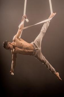 Zirkusartist auf den luftbändern mit starken muskeln auf dem hintergrund von rauch