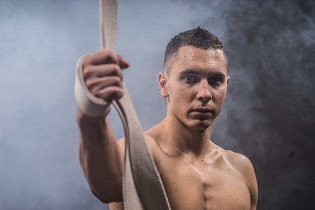 Zirkusartist auf den luftbändern mit starken muskeln auf schwarzem hintergrund