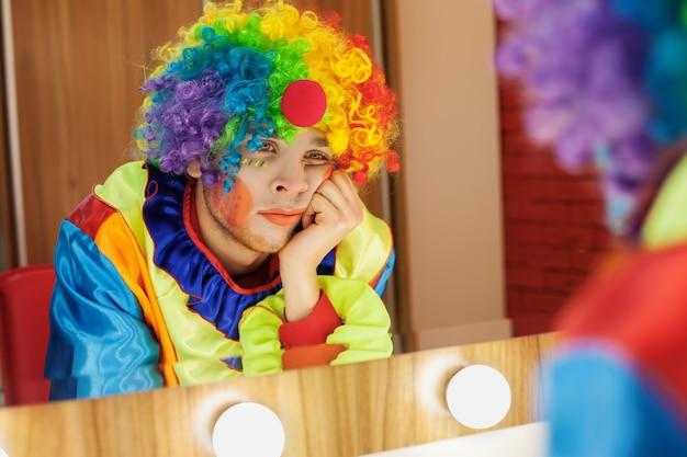 Zirkusclown schaut in einen spiegel im make-up-raum.