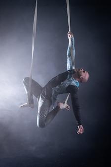 Zirkuskünstler an den luftgurten mit kostüm auf schwarz und geraucht.