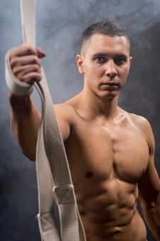 Zirkuskünstler, der luftbänder mit starken muskeln auf dem hintergrund von rauch hält. nahaufnahme