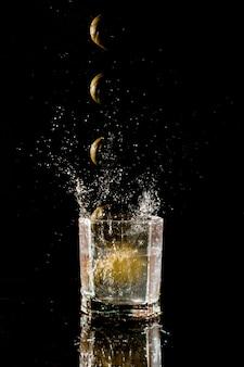 Zitrone fällt in ein glas